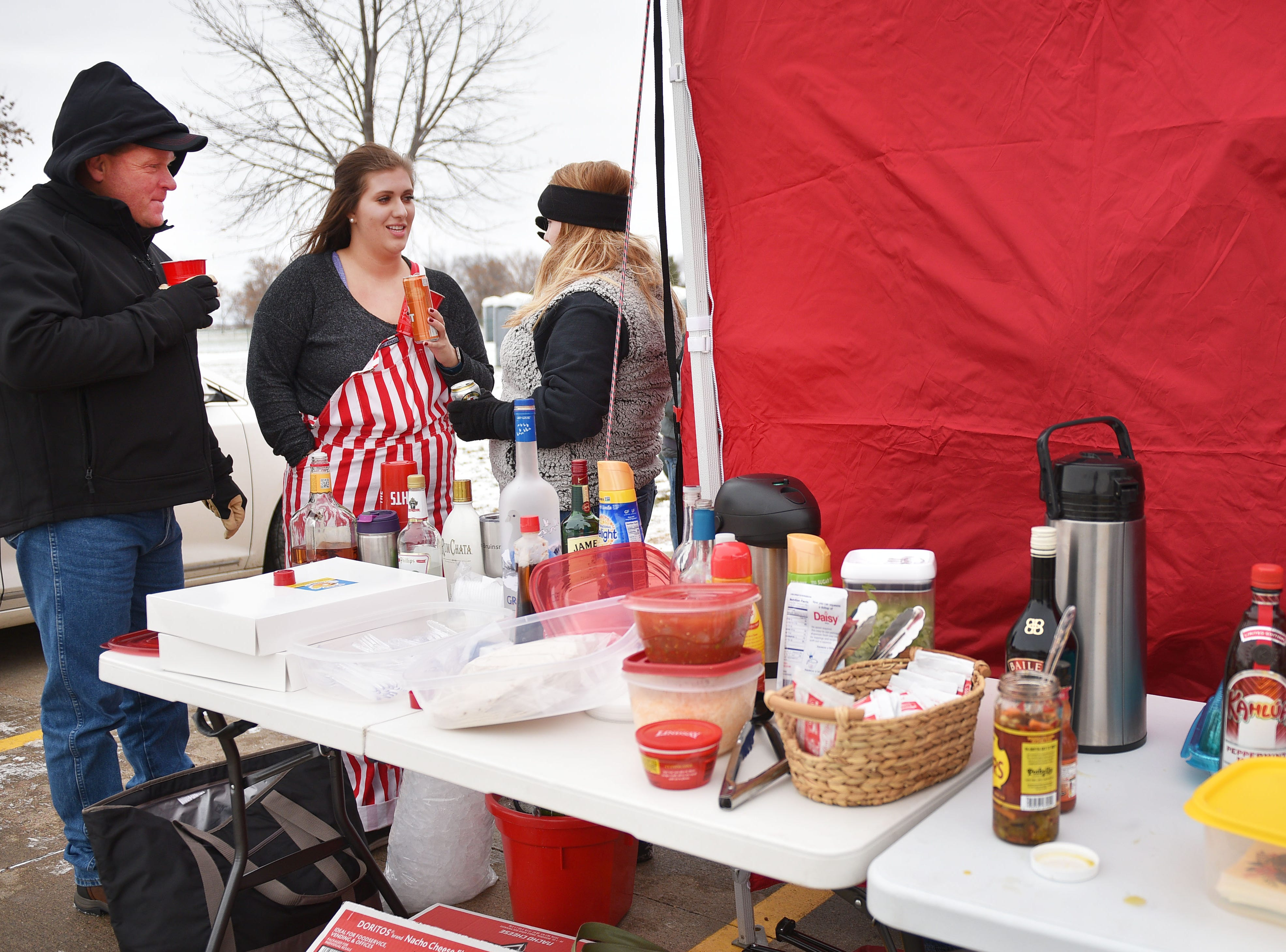 USD fans Scott Simons, from left, Zoey O'Brien and Leah Jeseritz tailgate before the game against Western Illinois Saturday, Nov. 10, at the DakotaDome in Vermillion.