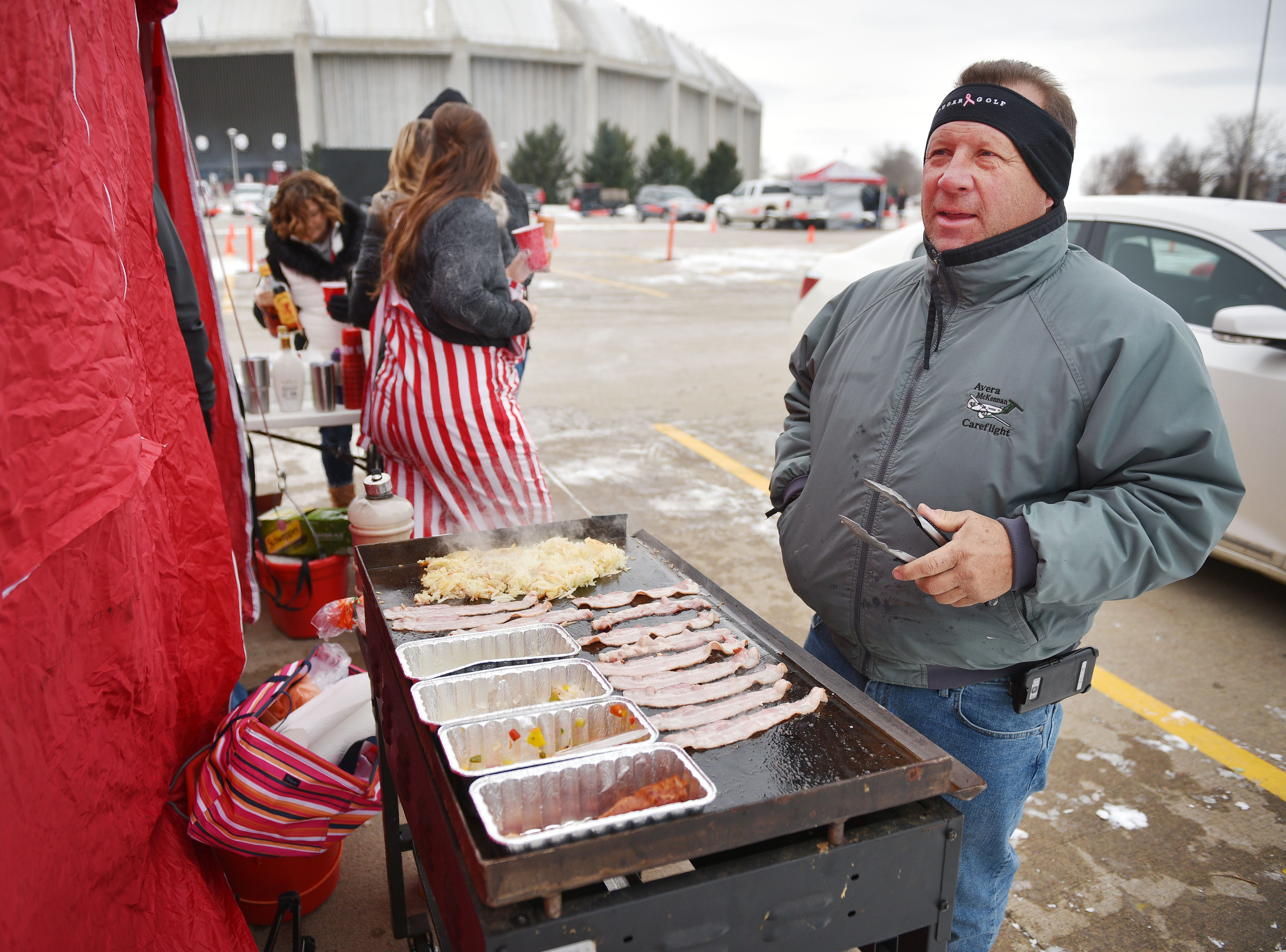USD fan Tom Leif cook bacon and hash browns for breakfast burritos during the USD tailgate before the game against Western Illinois Saturday, Nov. 10, at the DakotaDome in Vermillion.