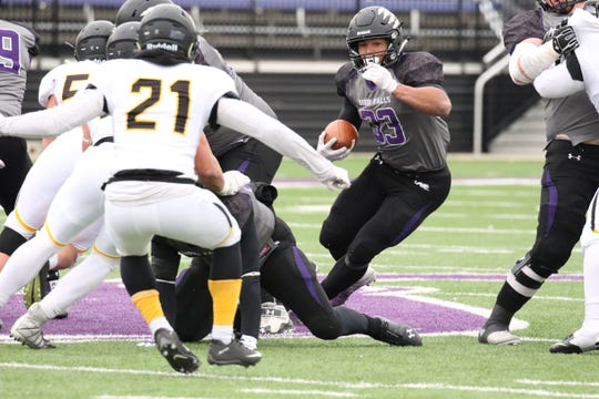 University of Sioux Falls RB, Gabriel Watson cuts into an opening as Kevin Ransom of Wayne State defends during Saturday's game in Sioux Falls.