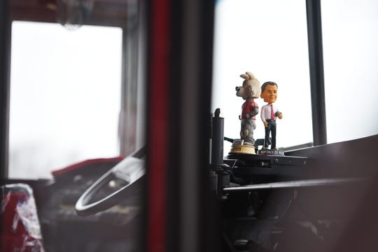 A Bob Nielson and Charlie the coyote bobble heads sit on the dash of a tailgating bus before the game against Western Illinois Saturday, Nov. 10, at the DakotaDome in Vermillion.