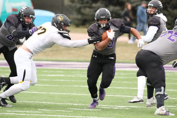 University of Sioux Falls RB, Gabriel Watson runs past the defense by Jacob Protzman of Wayne State during Saturday's game in Sioux Falls.