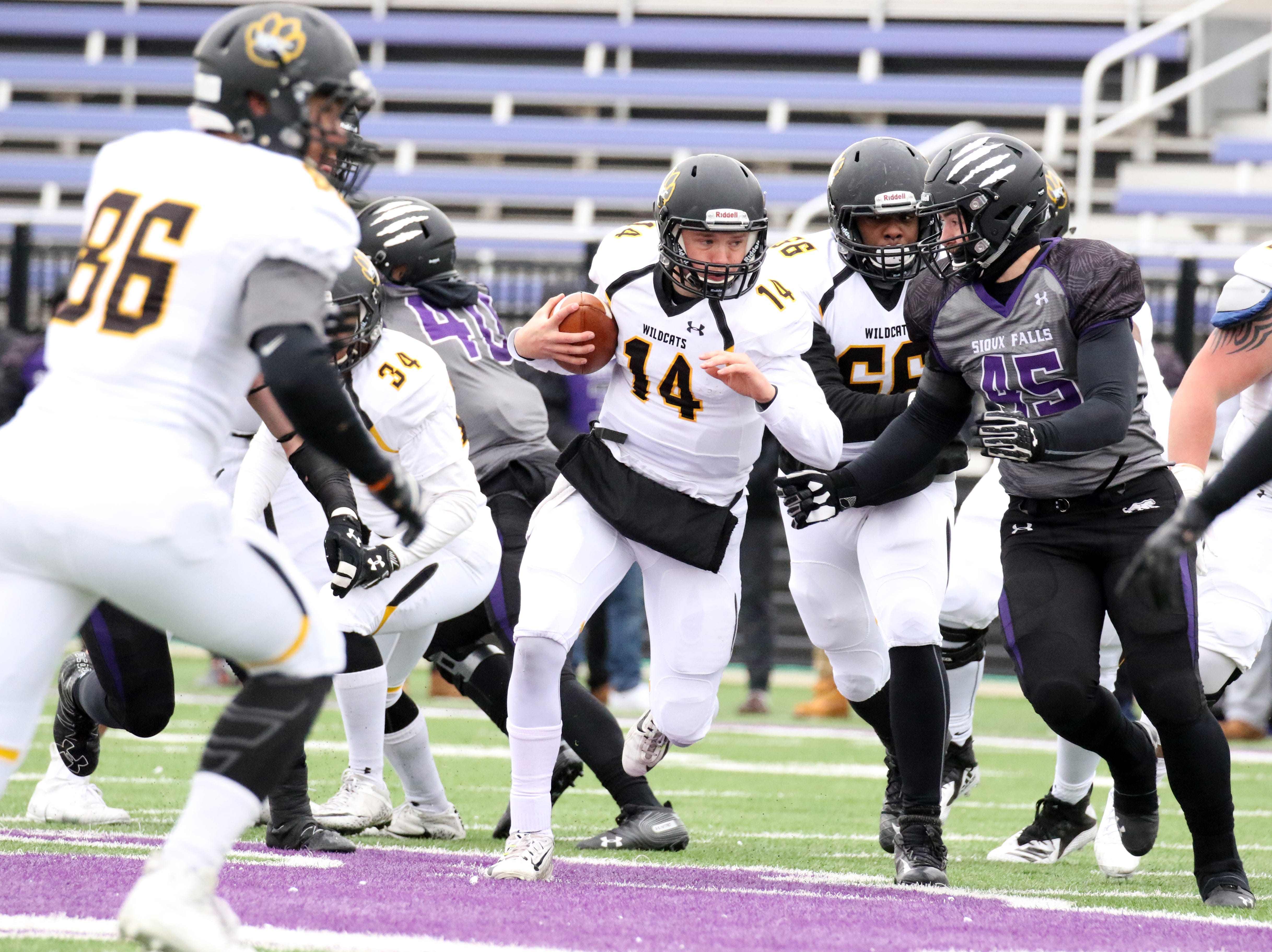 Wayne State QB, Alex Thramer looks to get past the defense of Joey Wehrkamp of the University of Sioux Falls during Saturday's game in Sioux Falls.