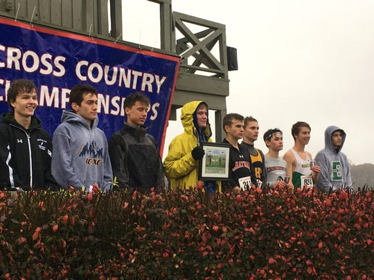 Robert E. Lee's Oliver Wilson-Cook, center, shows his first-place plaque during the awards ceremony for the Class 2 boys race at the VHSL Cross Country Championships on Friday, Nov. 9, 2018, at Great Meadow in The Plains, Va.