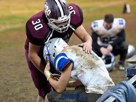 A Luray player comforts a Robert E. Lee after Lee falls to Luray in a Region 2B playoff opening round football game played in Luray on Friday, Nov. 9, 2018.