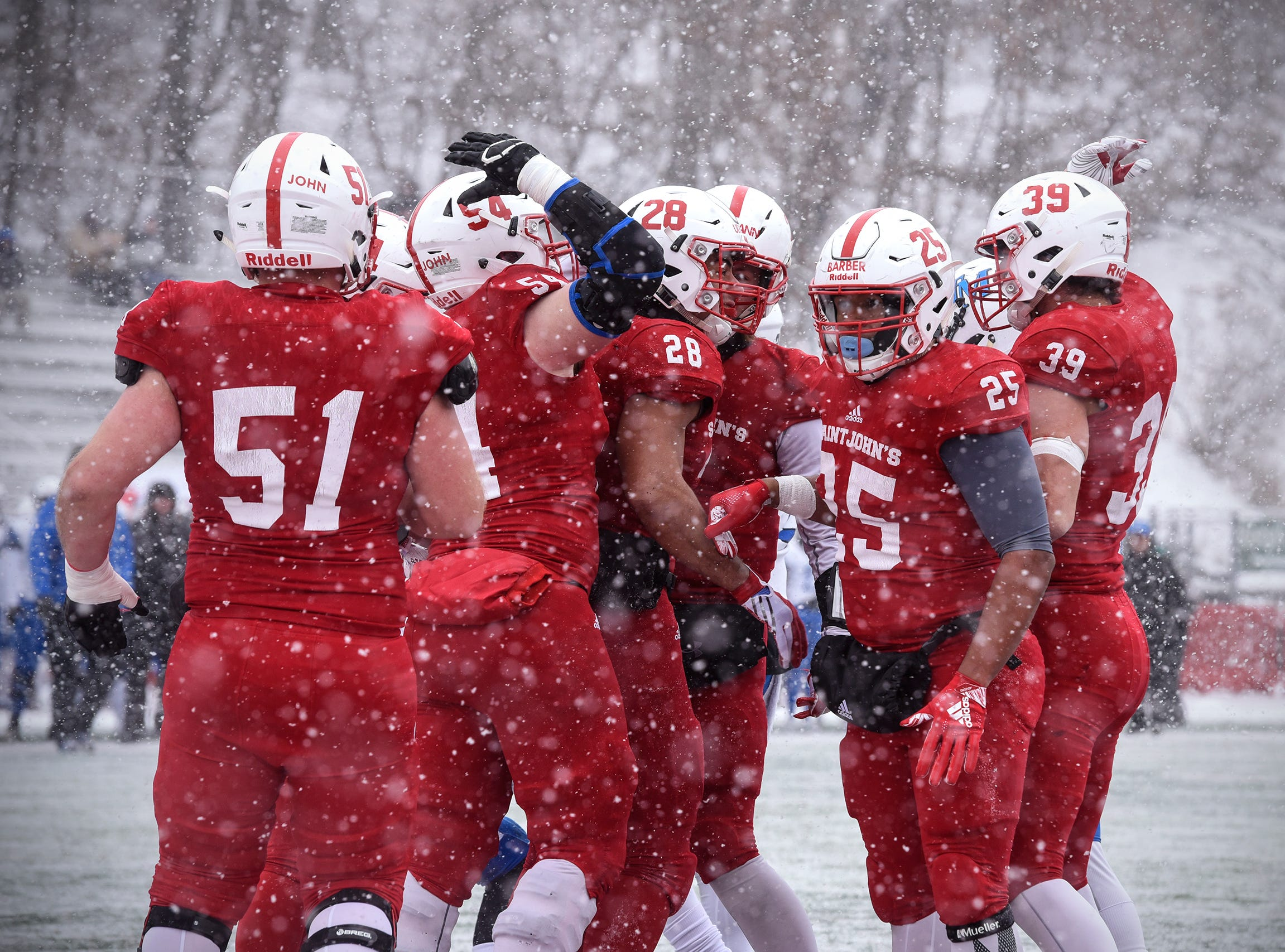 St. John's players celebrate a touchdown by Kenneth Udoibok during the first half of the Saturday, Nov. 10, game against Thomas More University at Clemens Stadium in Collegeville.