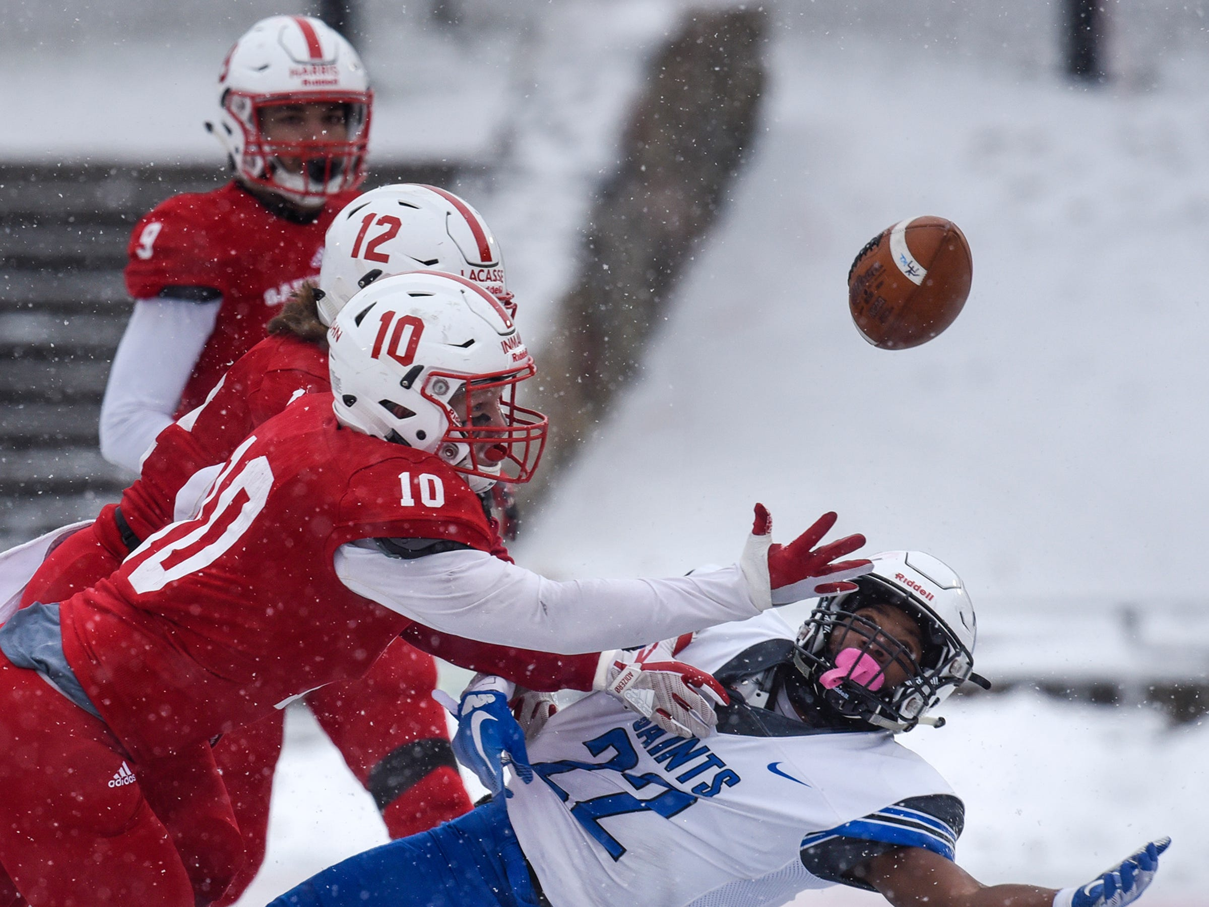 James Inman and Ryan LaCasse of St. John's try to break up a pass to Darrell Crenshaw during the first half of the Saturday, Nov. 10, game against Thomas More University at Clemens Stadium in Collegeville.