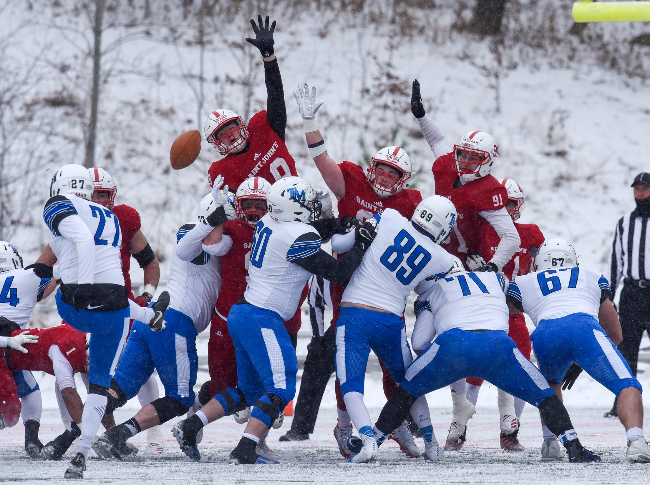 St. John's players leap in an attempt to block a kick during the first half of the Saturday, Nov. 10, game against Thomas More University at Clemens Stadium in Collegeville.