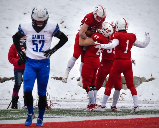St. John's players celebrate their first touchdown of the game during the first half of the Saturday, Nov. 10, game against Thomas More University at Clemens Stadium in Collegeville.
