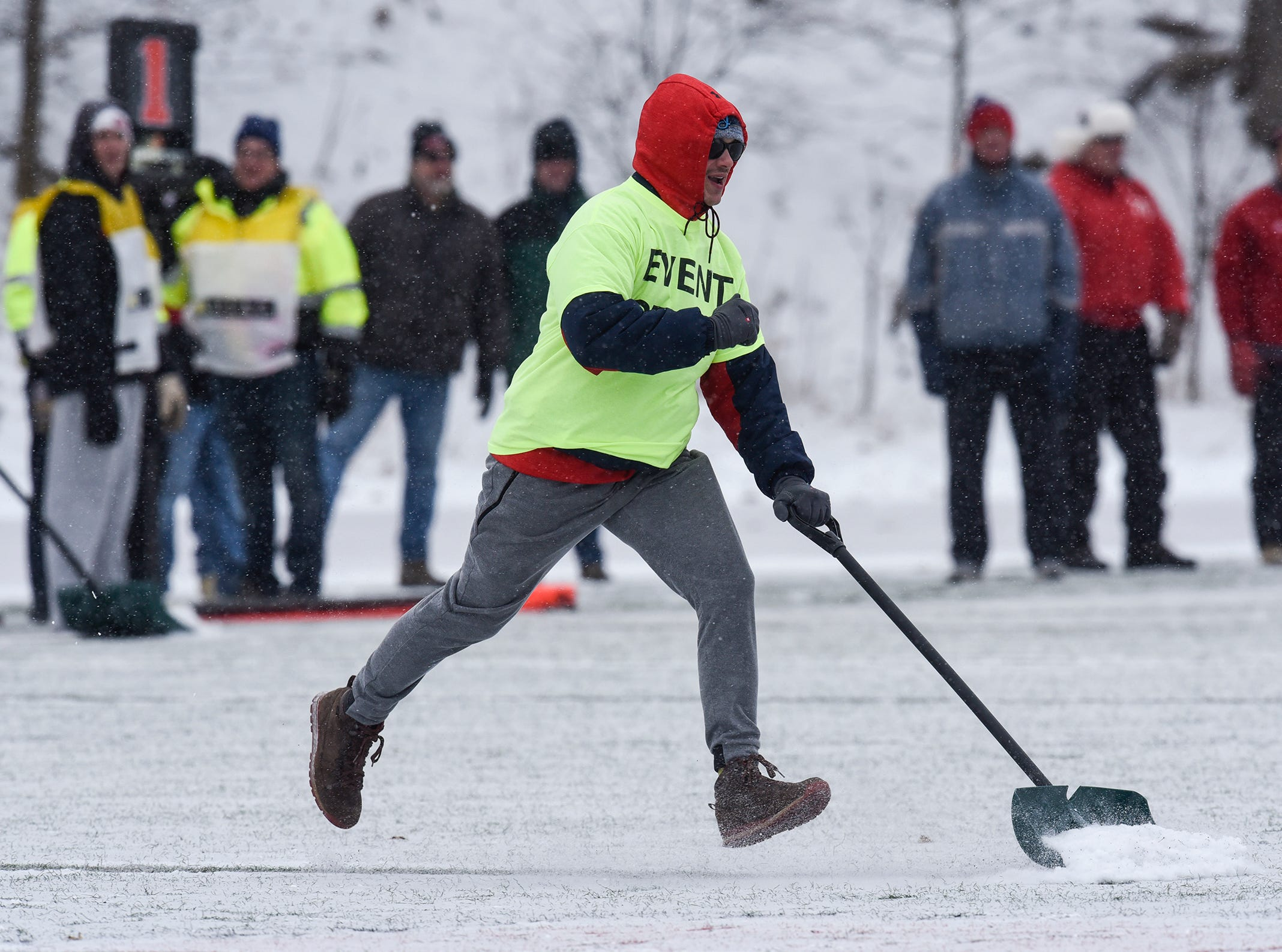 An event staff member cleans snow from a yard line marker during the first half of the Saturday, Nov. 10, game against Thomas More University at Clemens Stadium in Collegeville.
