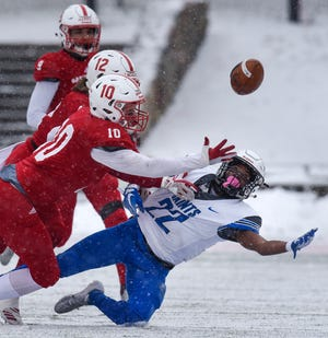 James Inman and Ryan LaCasse of St. John's try to break up a pass to Darrell Crenshaw during the first half of the Saturday, Nov. 10, game against Thomas Moore University at Clemens Stadium in Collegeville.