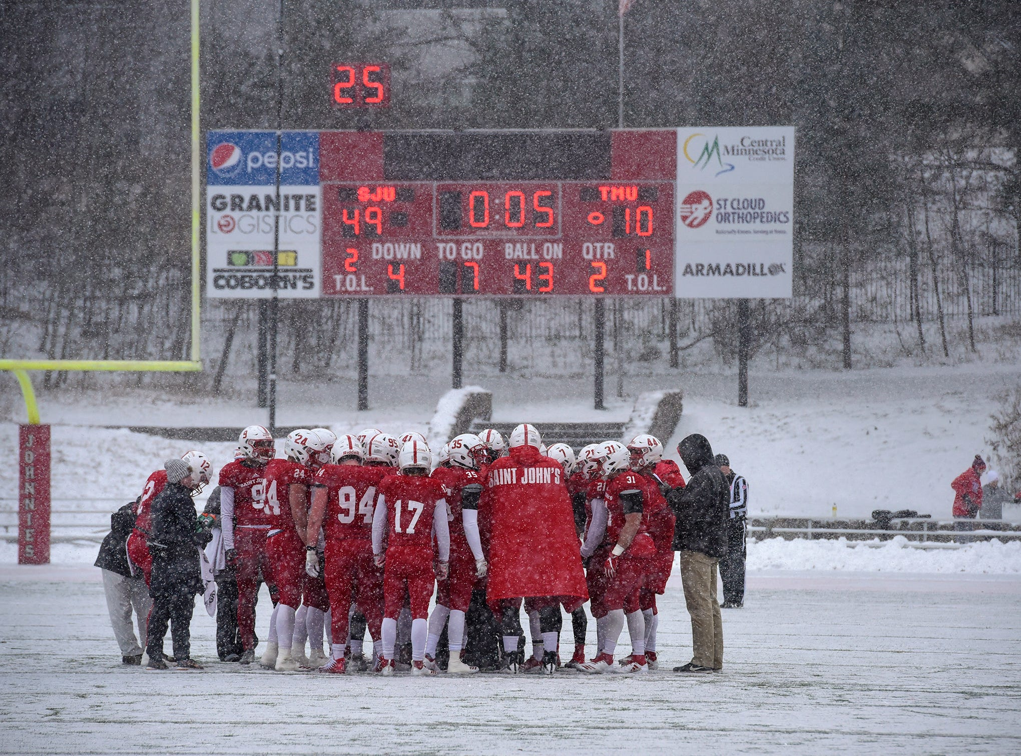 St. John's players gather during a timeout under heavy snowfall during the first half of the Saturday, Nov. 10, game against Thomas More University at Clemens Stadium in Collegeville.