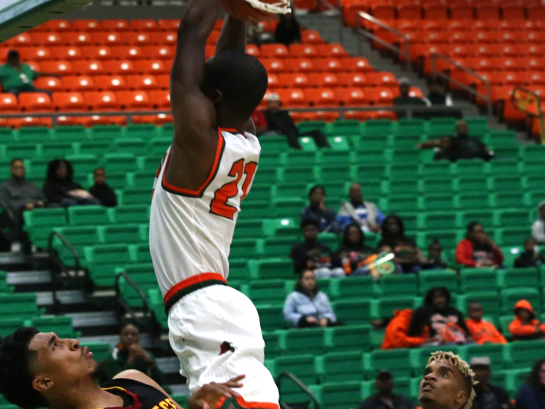 Florida A&M Rattlers guard Justin Ravenel dunks on a Tuskegee's Riley Hamilton in the first home game of the season on Saturday, Nov. 10.