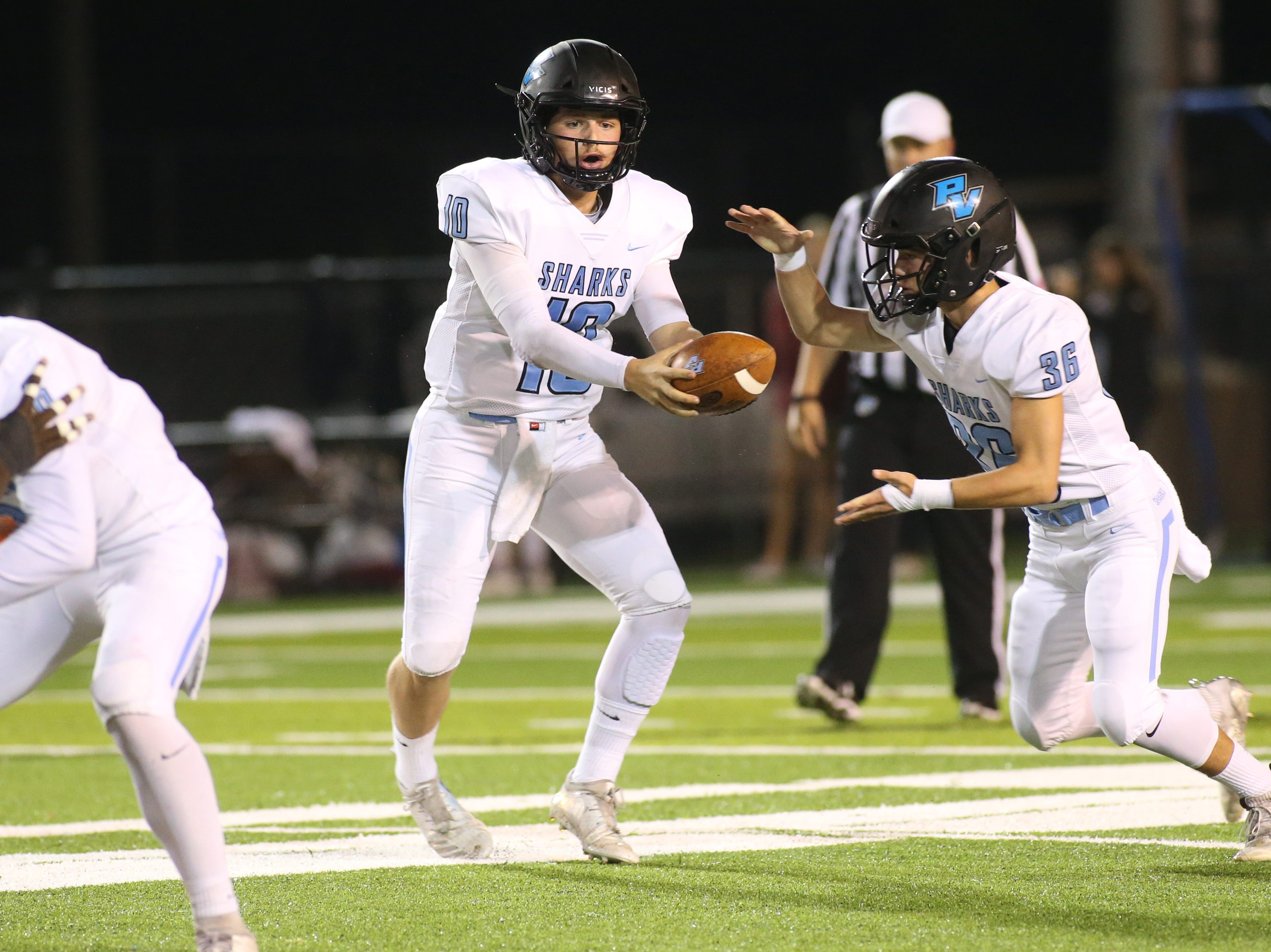 Ponte Vedra quarterback Jack Murrah (10) hands off the ball to running back Campbell Parker (36) as the Ponte Vedra Sharks face off against the Godby Cougars, in the Region 1-5A quarterfinal high school football playoff game at Gene Cox Stadium, Friday, Nov. 9, 2018.