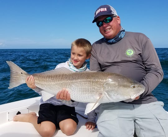 Noah, 6, and grandfather Capt. Glyn Austin of Going Coastal charters in Sebastian hoist one of the several oversized redfish caught and released with angler Doug Blanchard Thursday in Sebastian Inlet.
