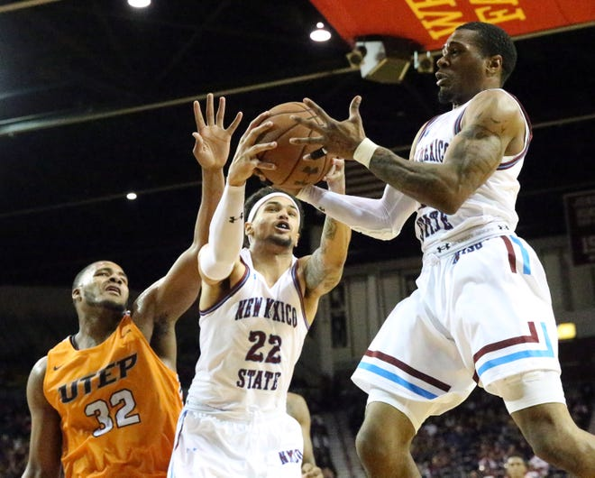 NMSU's Eli Chuha, 22, and A.J. Harris, 12 come down with a defensive rebound against Efe Odigie, 32, of UTEP Friday night in the Pan American Center.