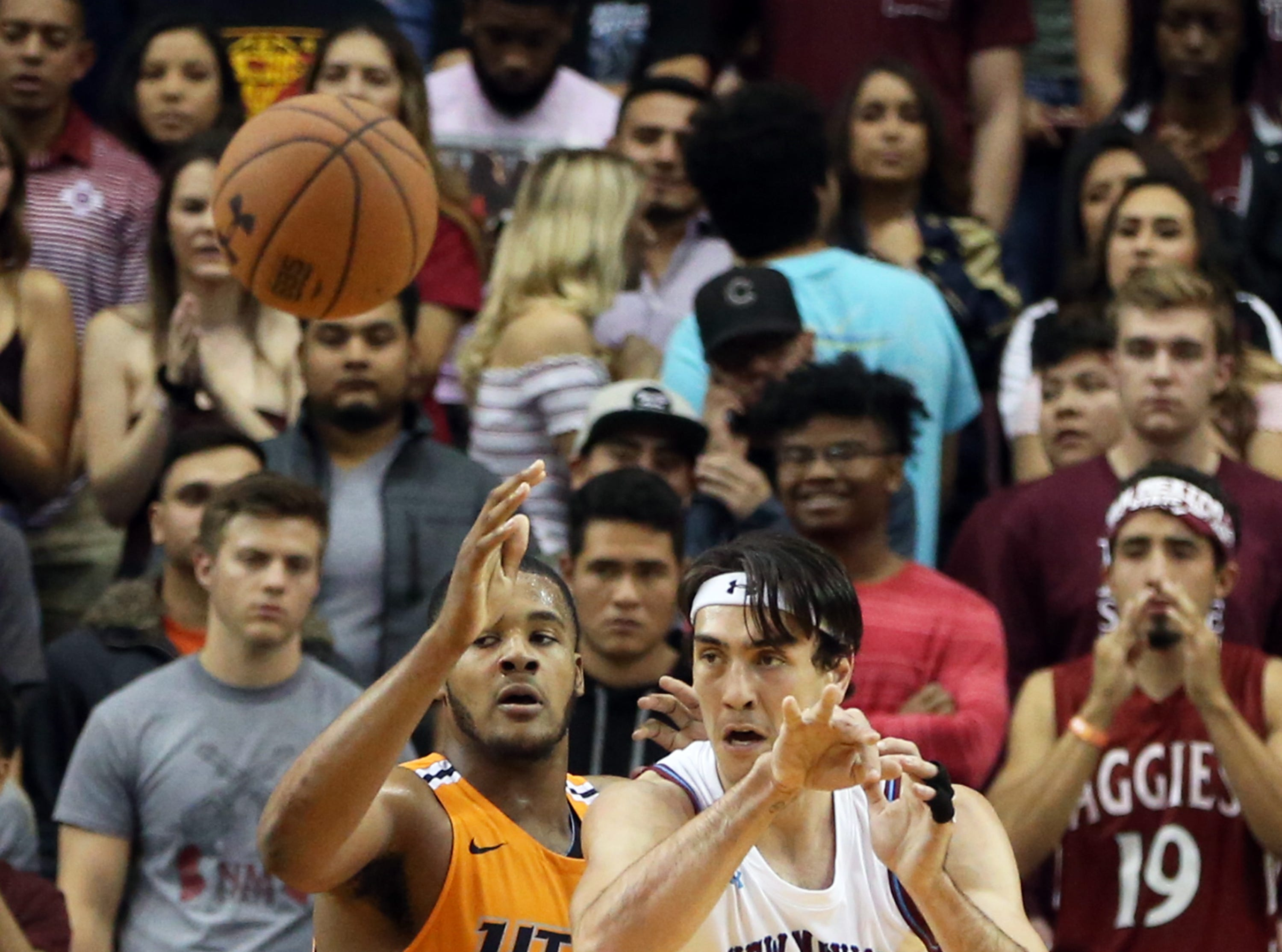 Ivan Aurrecoechea, 15, of NMSU finds an outlet while getting pressure from UTEP's Efe Odigie, 32, Friday night.