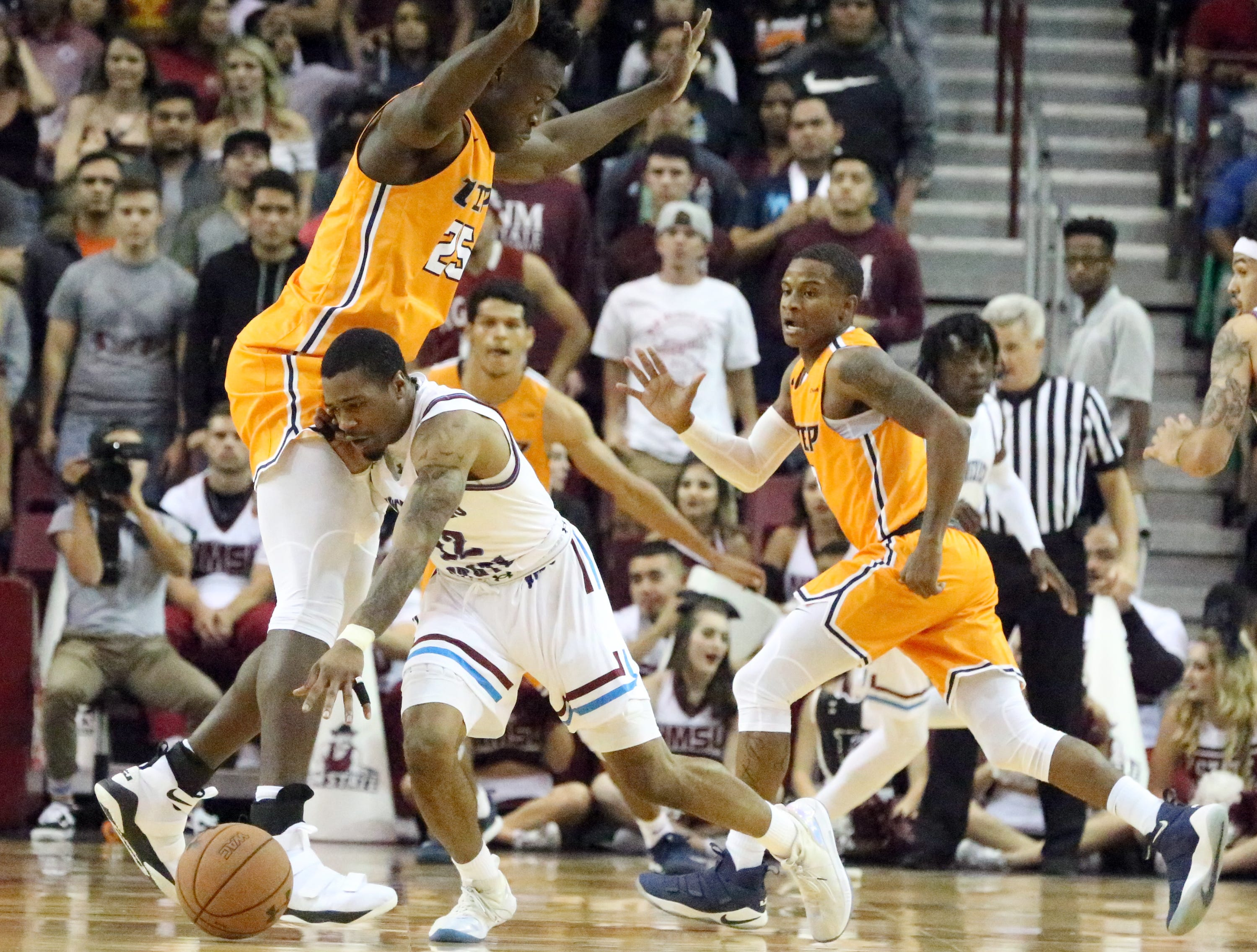 AJ Harris, 12, of NMSU drives into UTEP's Kaosi Ezeagu 25, of UTEP Friday night.