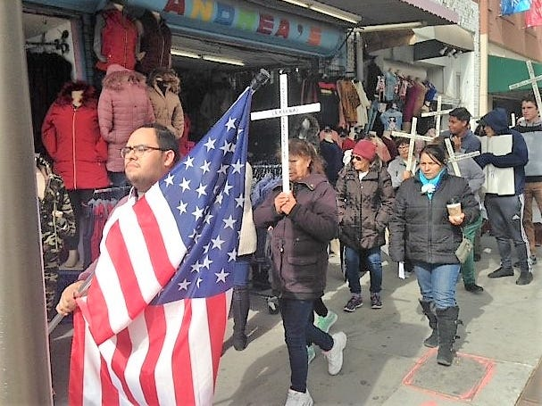 Alonso Sanchez, 19, of Chamberino, N.M., carries an American flag as he and other protesters pass by South El Paso Street stores during a Saturday, Nov. 10, 2018, immigration-policy protest march in Downtown El Paso.