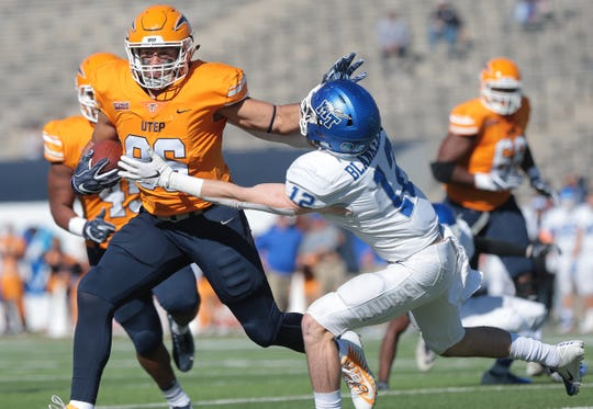 UTEP tight end Josh Weeks stiff arms Middle Tennessee's Reed Blankenship after a long gain Saturday at Sun Bowl Stadium.