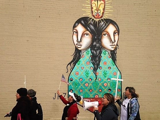 Immigration-policy protesters march Saturday, Nov. 10, 2018, past a mural near South El Paso Street in Downtown El Paso on their way to the Chihuahuita neighborhood.