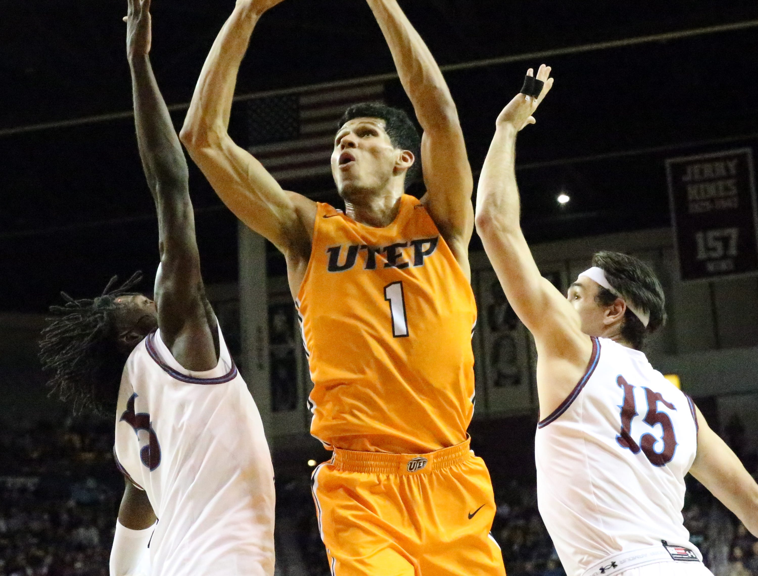 UTEP's Paul Thomas, 1, shoots against Clayton Henry, 5, and Ivan Aurrecoechea, 15 of NMSU Friday night.