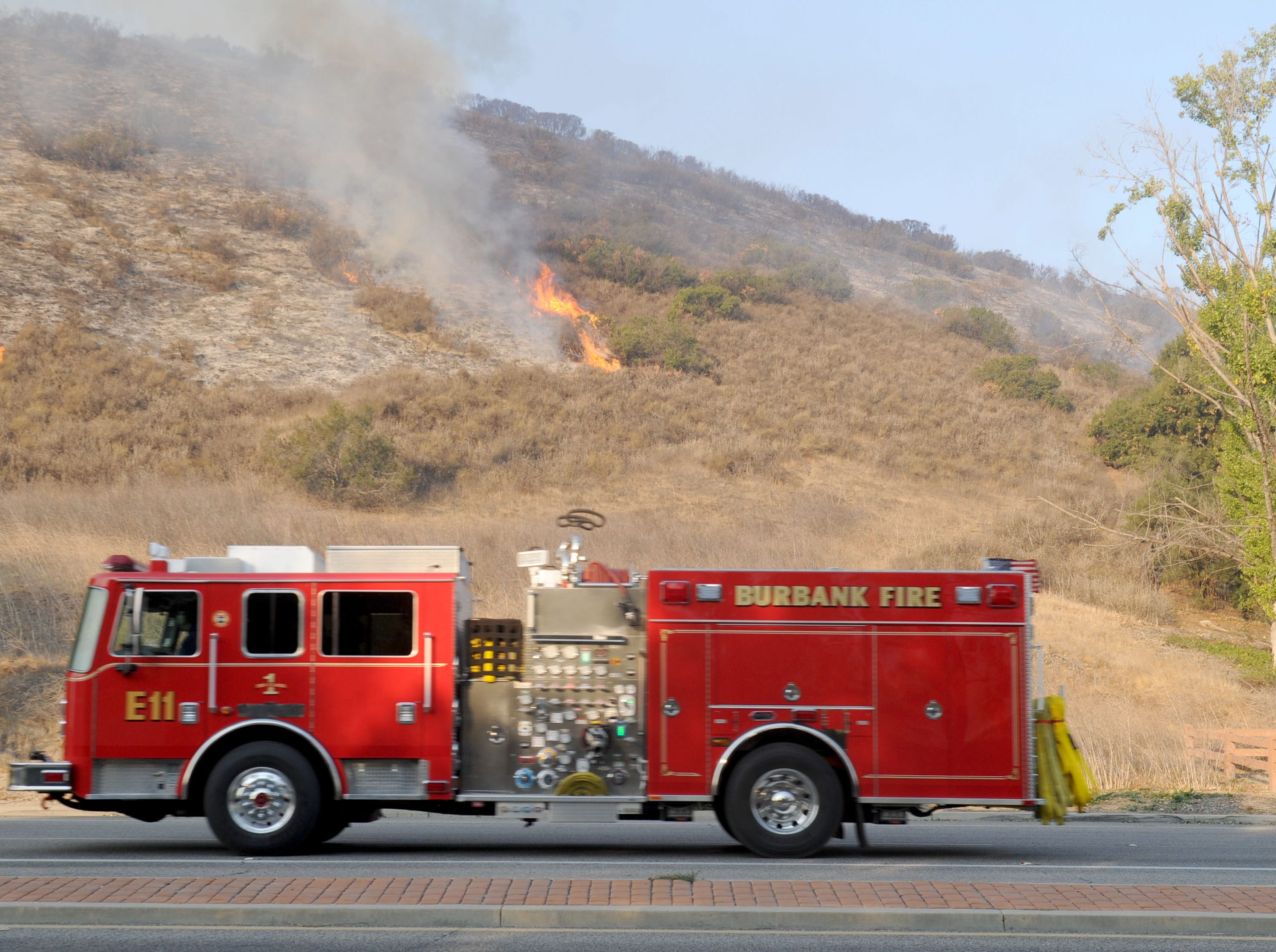 A fire truck passes a small brush fire burning Saturday in Oak Park. The Woolsey Fire continued to burn Saturday.