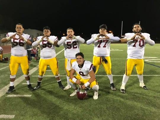 The Oxnard offensive line of Jacob Pech, Juan Ramos (left to right), Logan Simmons, Matthew Cortez and Alex Mirafuentez celebrates earning the Yellowjackets' first sectional semifinal in 16 years after a 34-31 win over Valencia-West Ranch on Friday. Quarterback Vincent Walea poses in front.