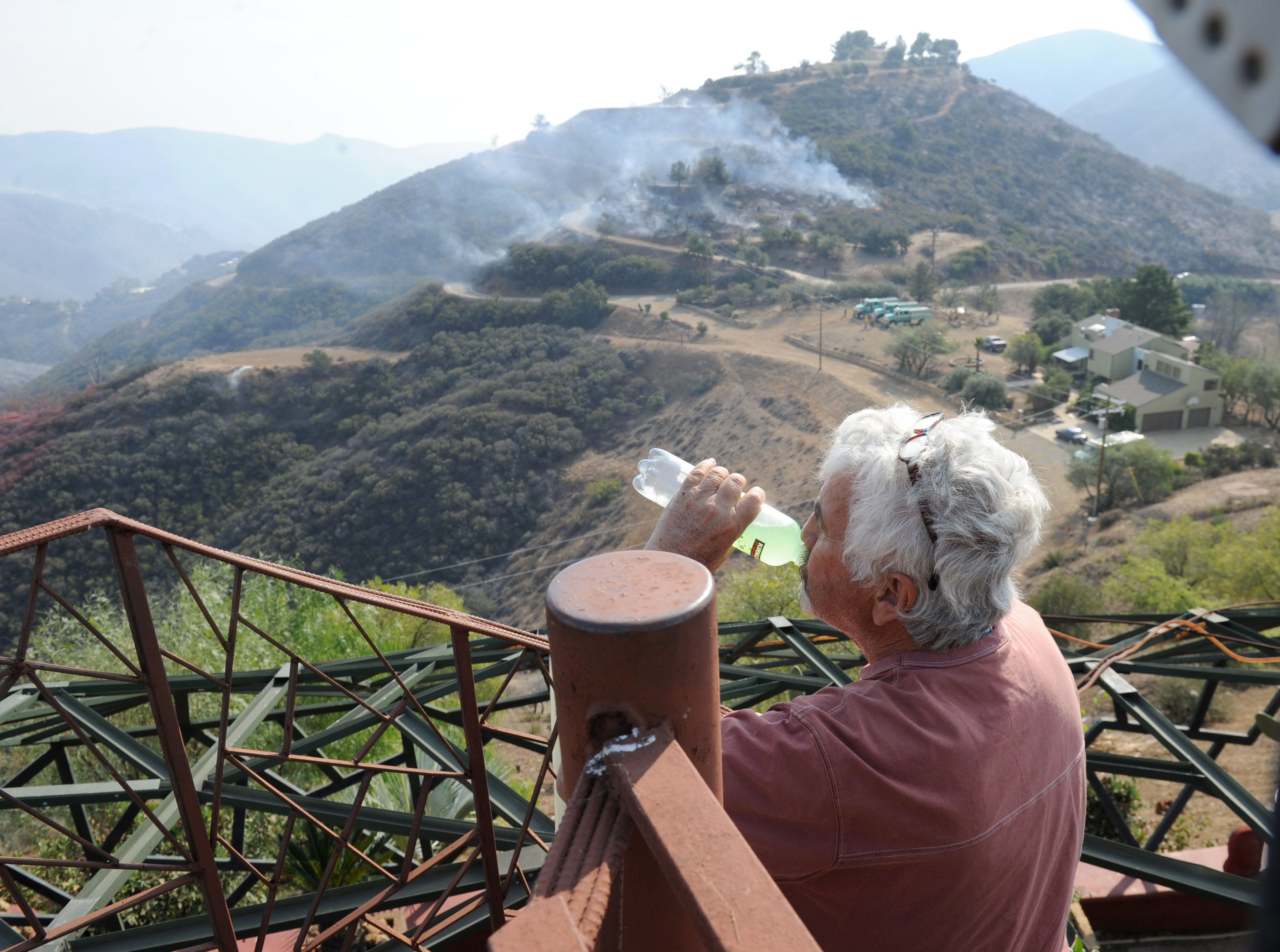 Rick Mecagni looks at the mountains surrounding his house at Mipolomol and Cotharin roads in Ventura County. The Woolsey Fire continued to burn in the area Saturday.