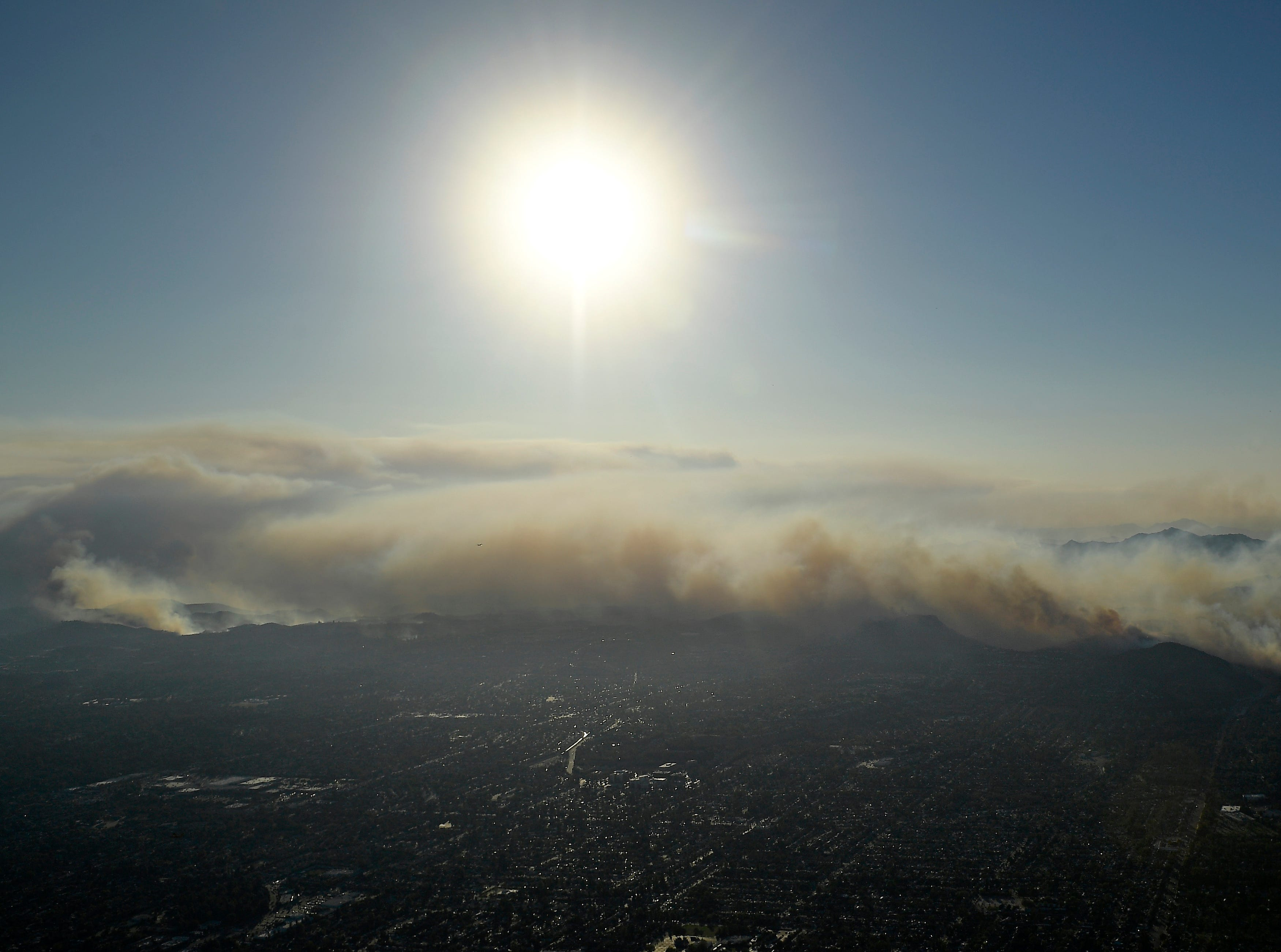 The Woolsey and Hill fires burn toward the Pacific Ocean as seen Friday from a helicopter over Chatsworth.