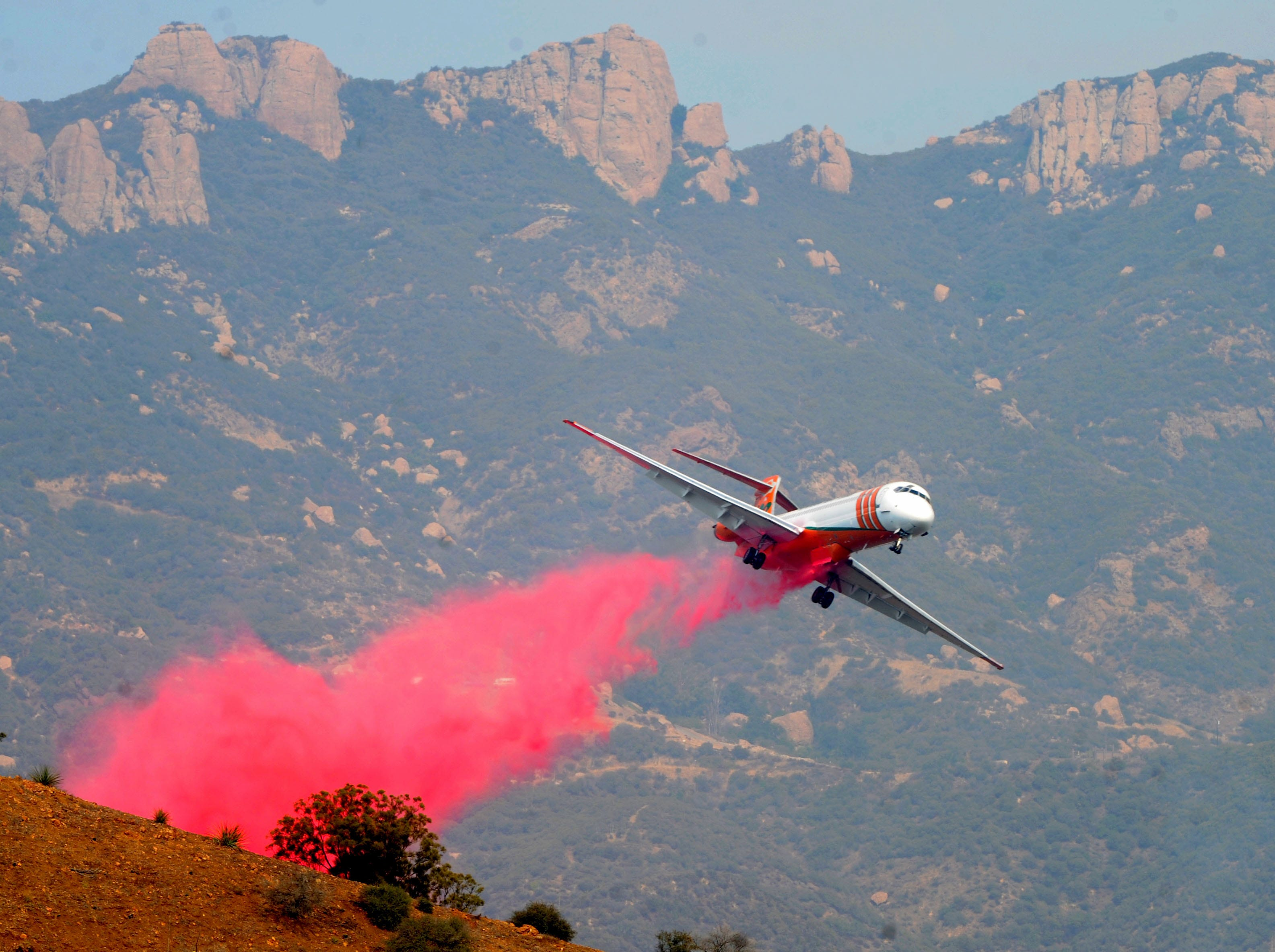 An airplane drops fire retardant Saturday near Mipolomol and Cotharin roads in the mountains of Ventura County.
