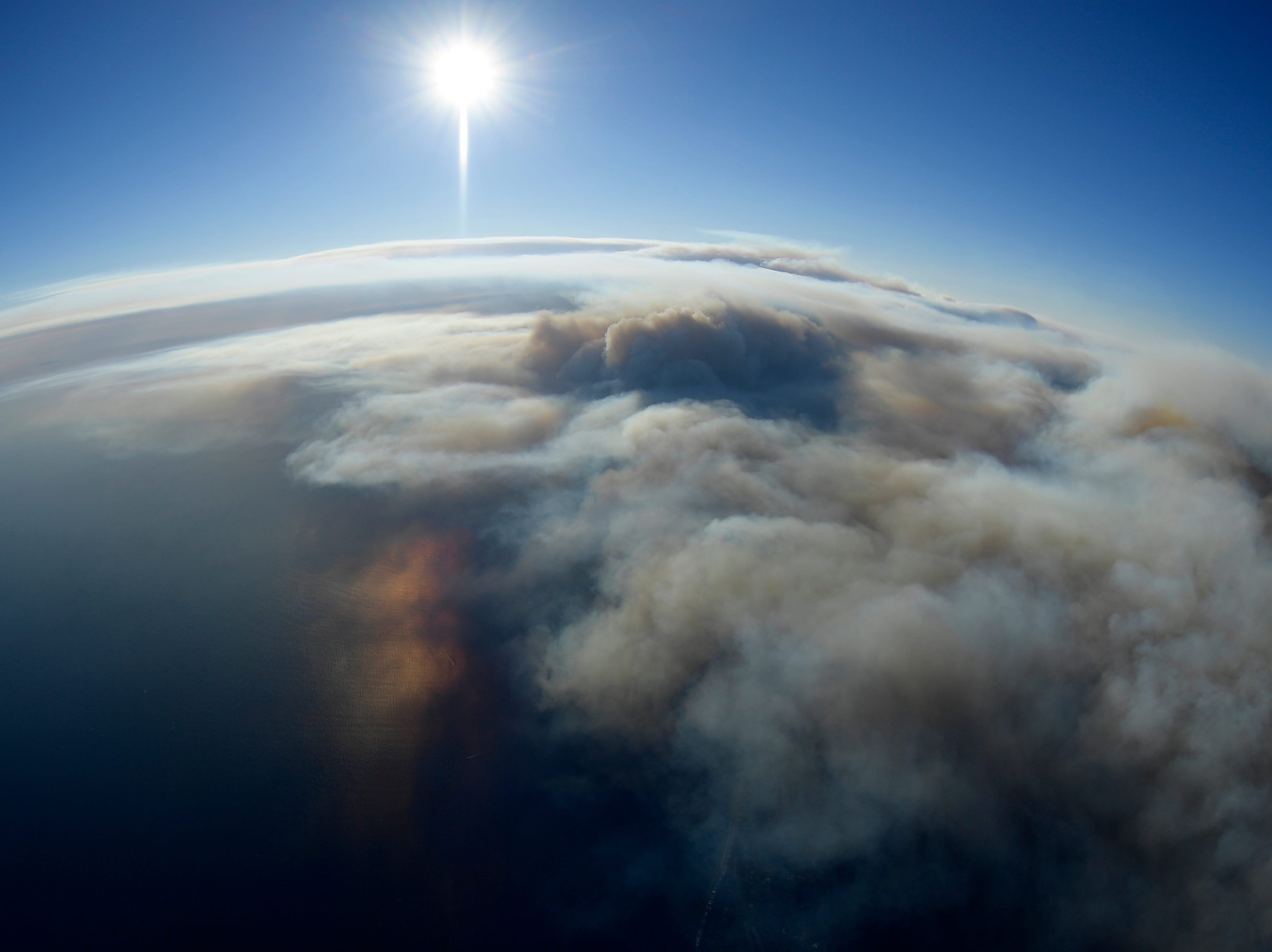 Smoke rises as the Woolsey and Hill fires burn toward the Pacific Ocean on Friday, as seen from a helicopter over Malibu.