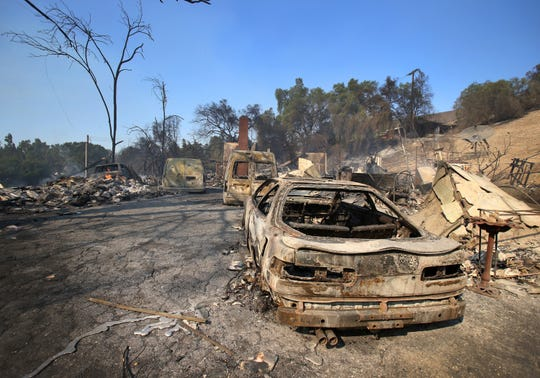 A Hillcrest and Amon drives in Thousand Oaks destroyed cars and a chimney sit Friday. The Woolsey Fire came through the area Thursday night.