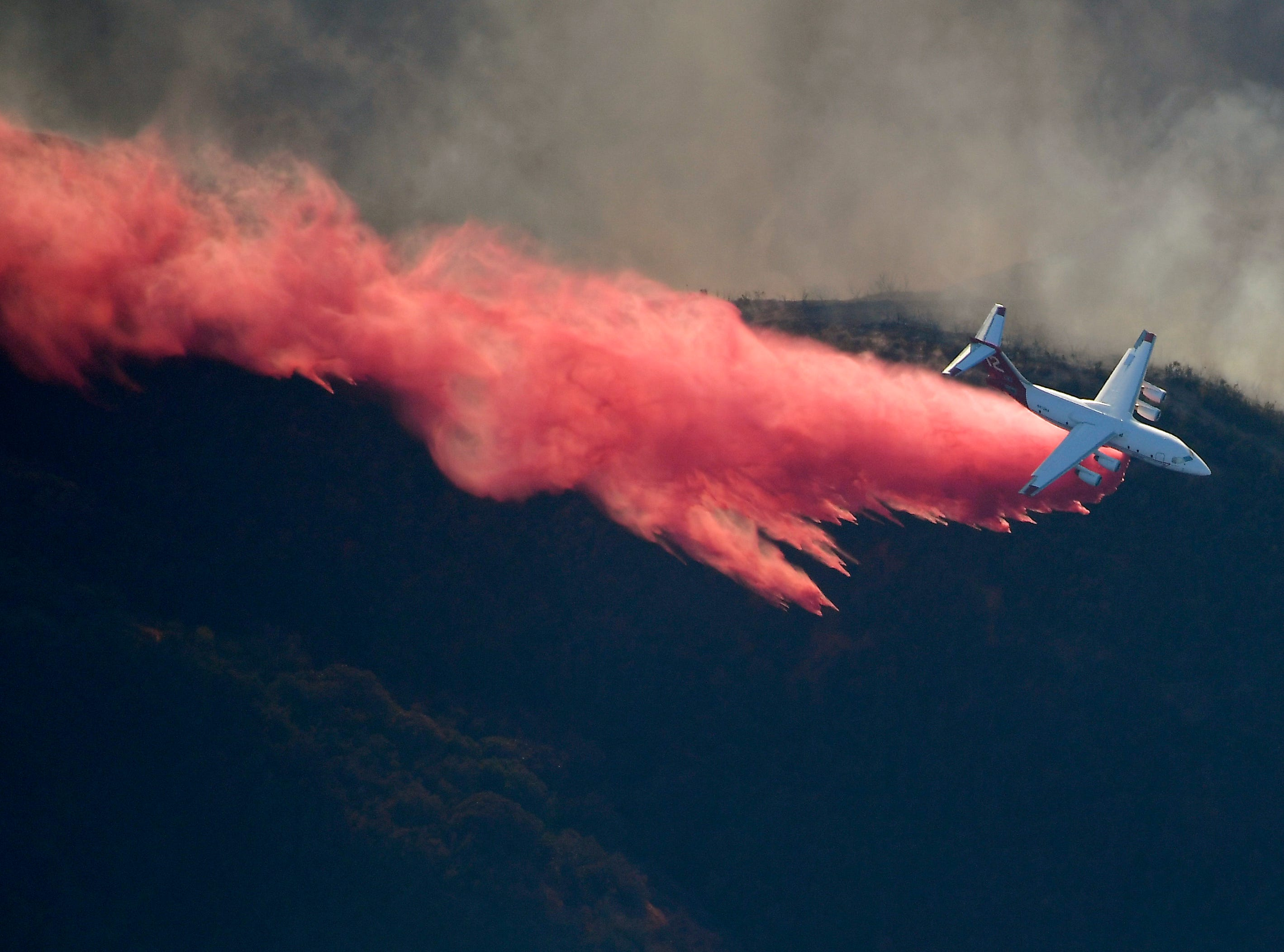 An air tanker drops flame retardant to protect homes from the Woolsey Fire on Friday in Calabasas.
