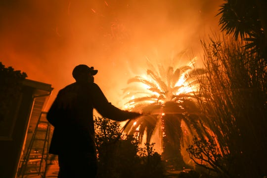 Park Billow sprays water on the hot spots in his backyard as the Woolsey Fire burns in Malibu on Friday.
