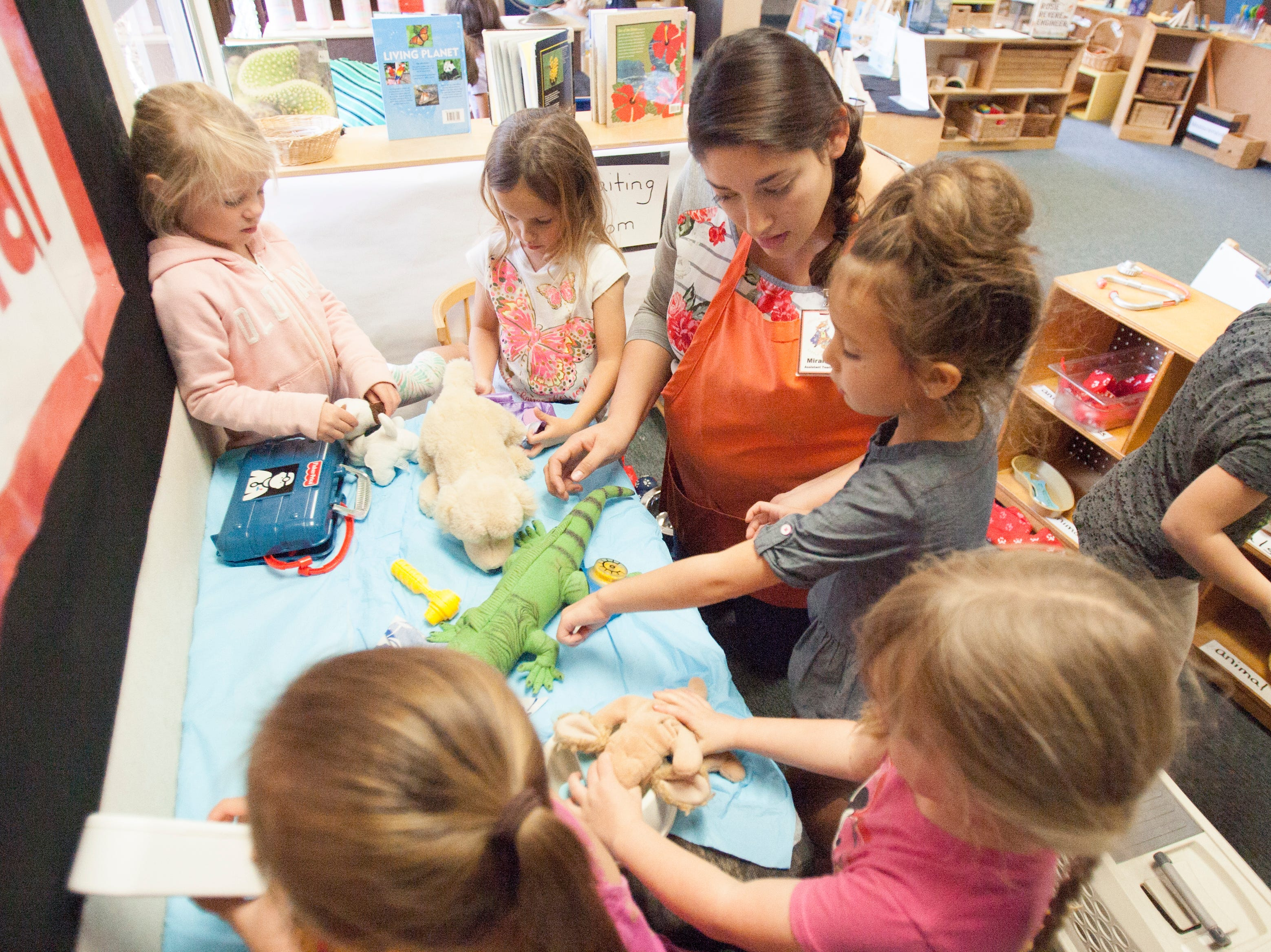 Assistant teacher Mirand Perez plays veterinary hospital with children at the Ventura College child care center. New federal funding is on the way.