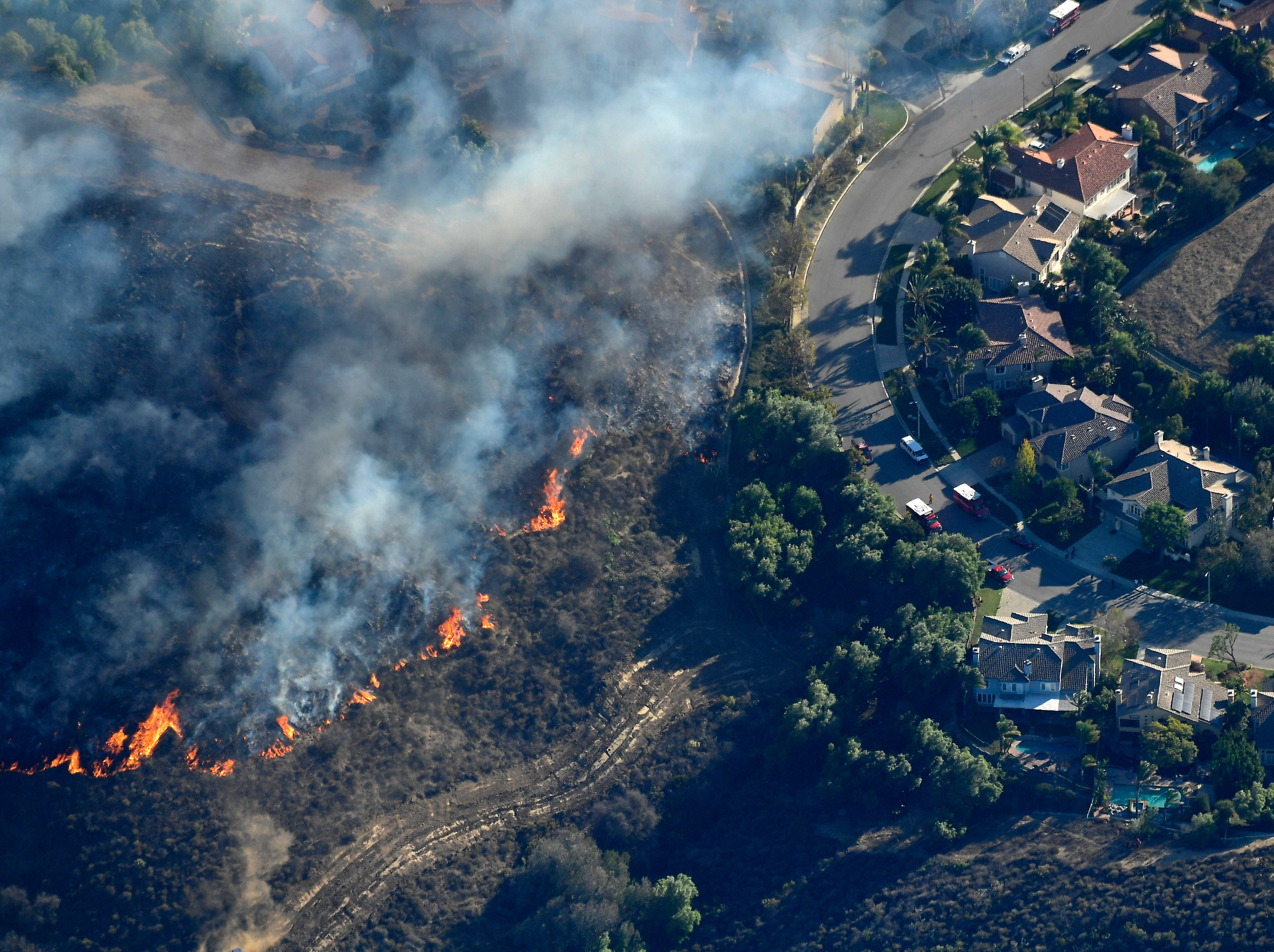 The Woolsey Fire burns toward homes Friday in Calabasas on its way to Malibu after starting near Simi Valley.