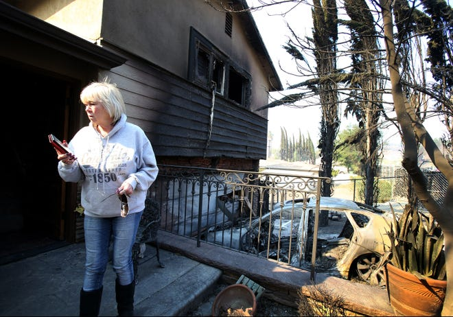 Shirley Hertel talks to her daughter Sara Evenson Friday as she assesses the damage to her home on Hillcrest Drive in Thousand Oaks. In the driveway is Evenson's car that was destroyed during Thursday night's fire. The home was saved but had significant damage to the outside and inside.