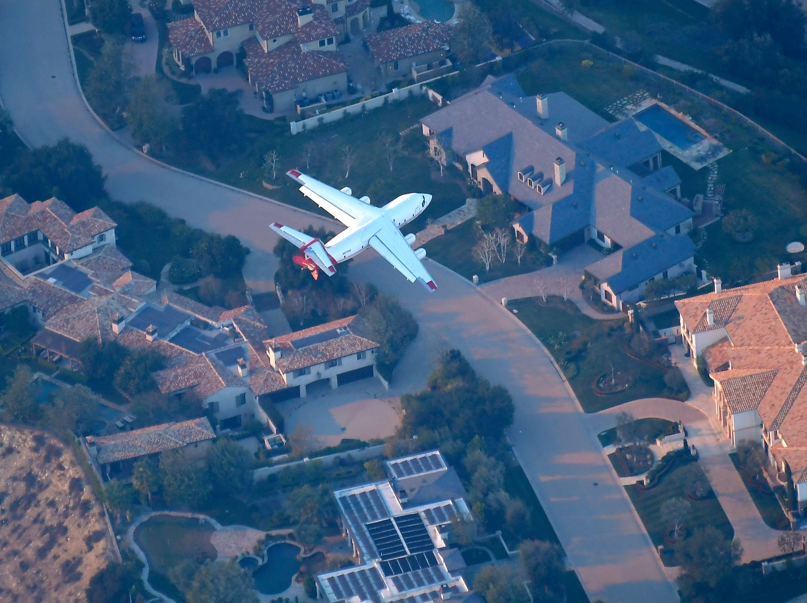 An air tanker gets ready to drop flame retardant to protect multimillion dollar homes in Calabasas from the Woolsey Fire on Friday.