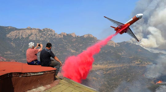 Rick Mecagni, left, and his friend Juan Grenados watch an airplane drop fire retardant near Mecagni's house at Mipolomol and Cotharin roads in the mountains of Ventura County in November 2018.