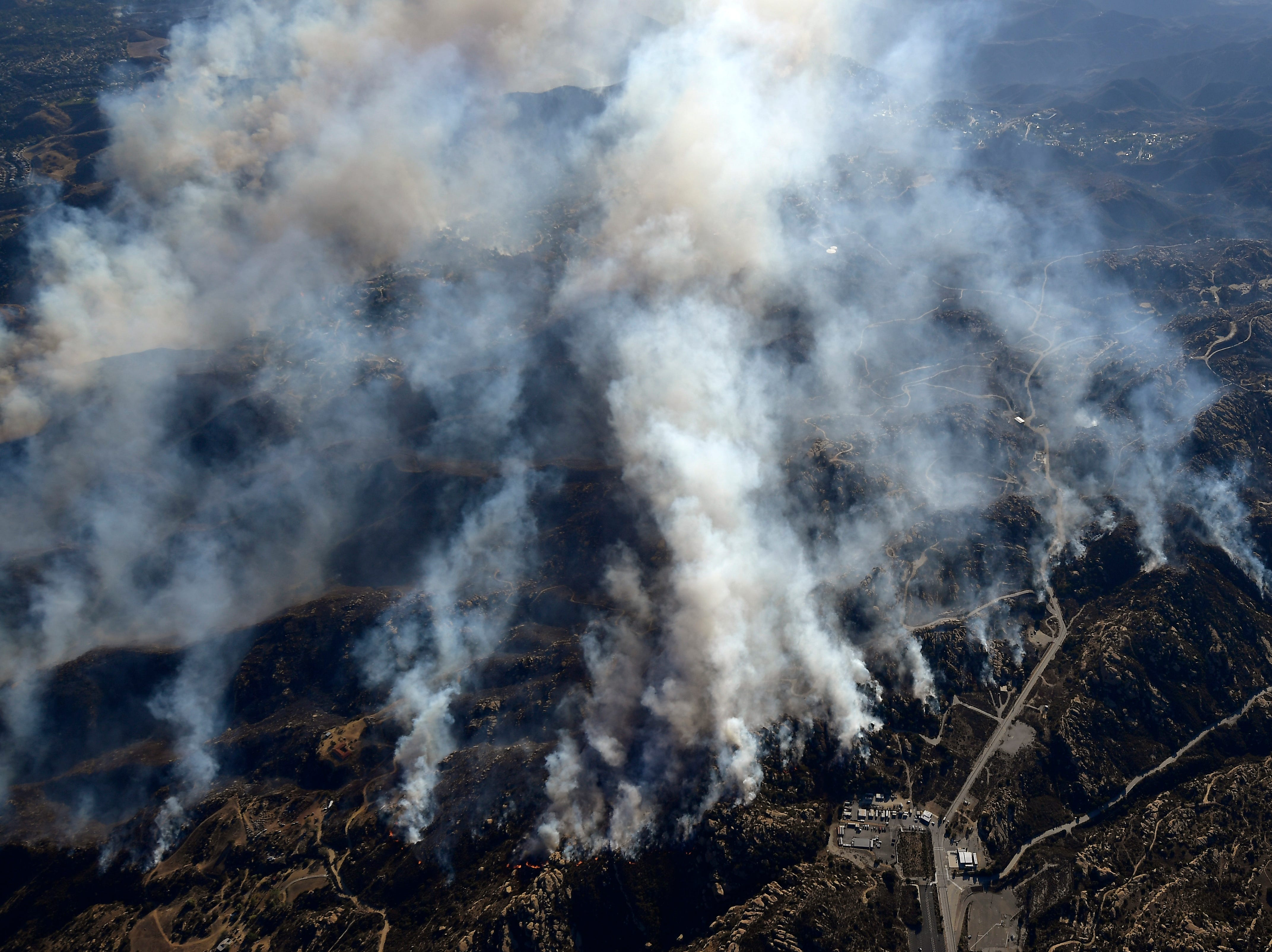 Smoke rises from the Woolsey Fire on Friday, as seen from a helicopter over Chatsworth.