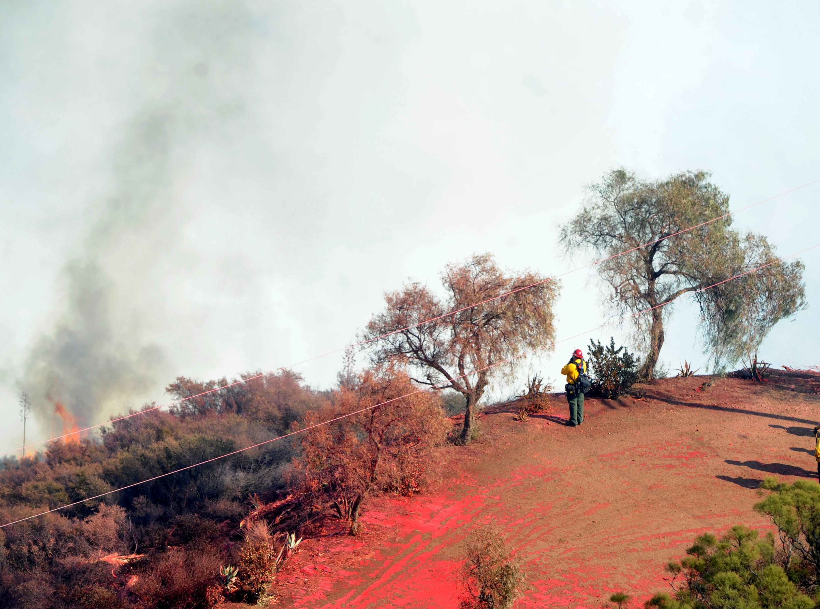 Firefighters watch the fire come up the mountain at Mipolomol and Cotharin roads in Ventura County. The Woolsey Fire continued to burn Saturday.