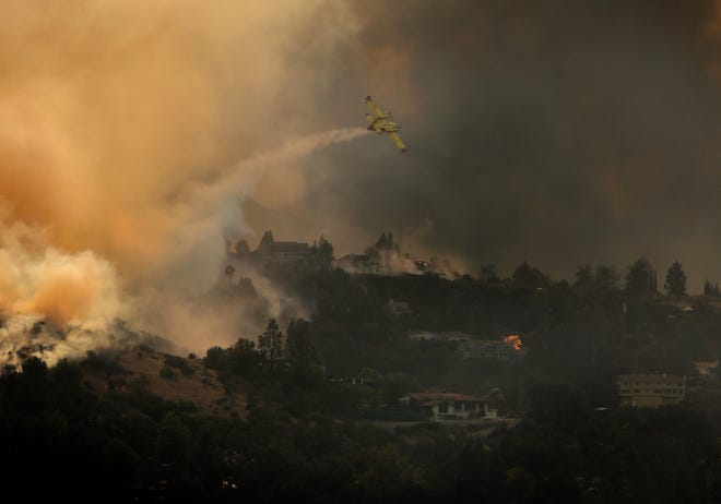 A plane drops a load of water on one of the hot spots threatening property in Agoura Hills on Friday.