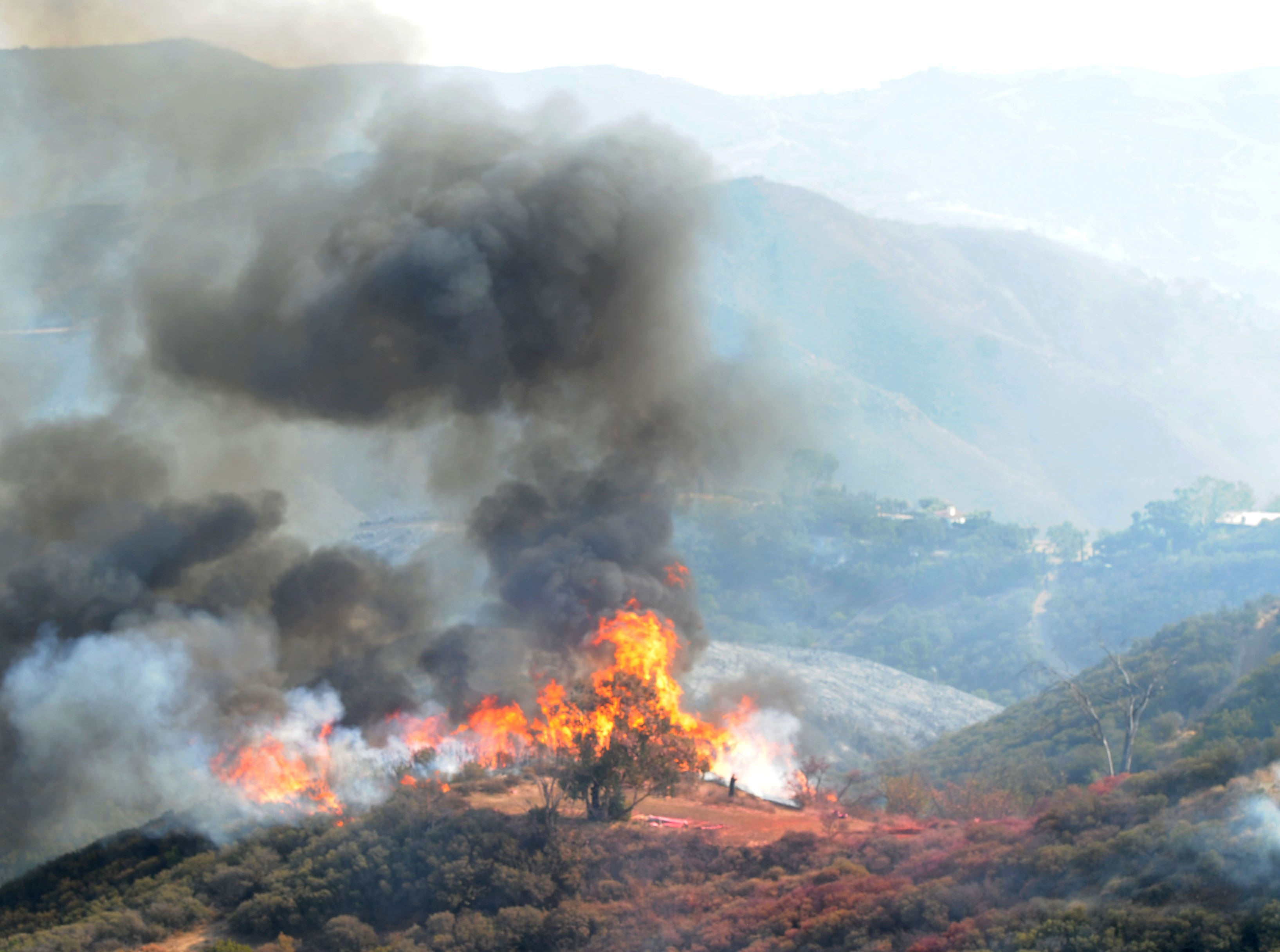 The Woolsey Fire burns Saturday in the mountains near Mipolomol and Cotharin roads in an unincorporated portion of Ventura County.