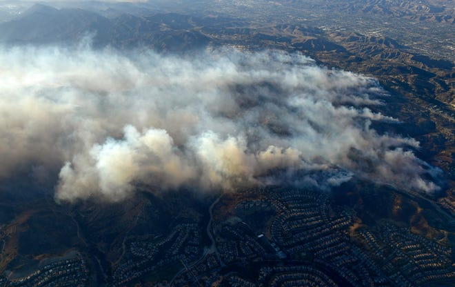 Smoke rises as the Woolsey and Hill fires burn toward the Pacific Ocean on Friday, as seen from a vantage point over Calabasas.