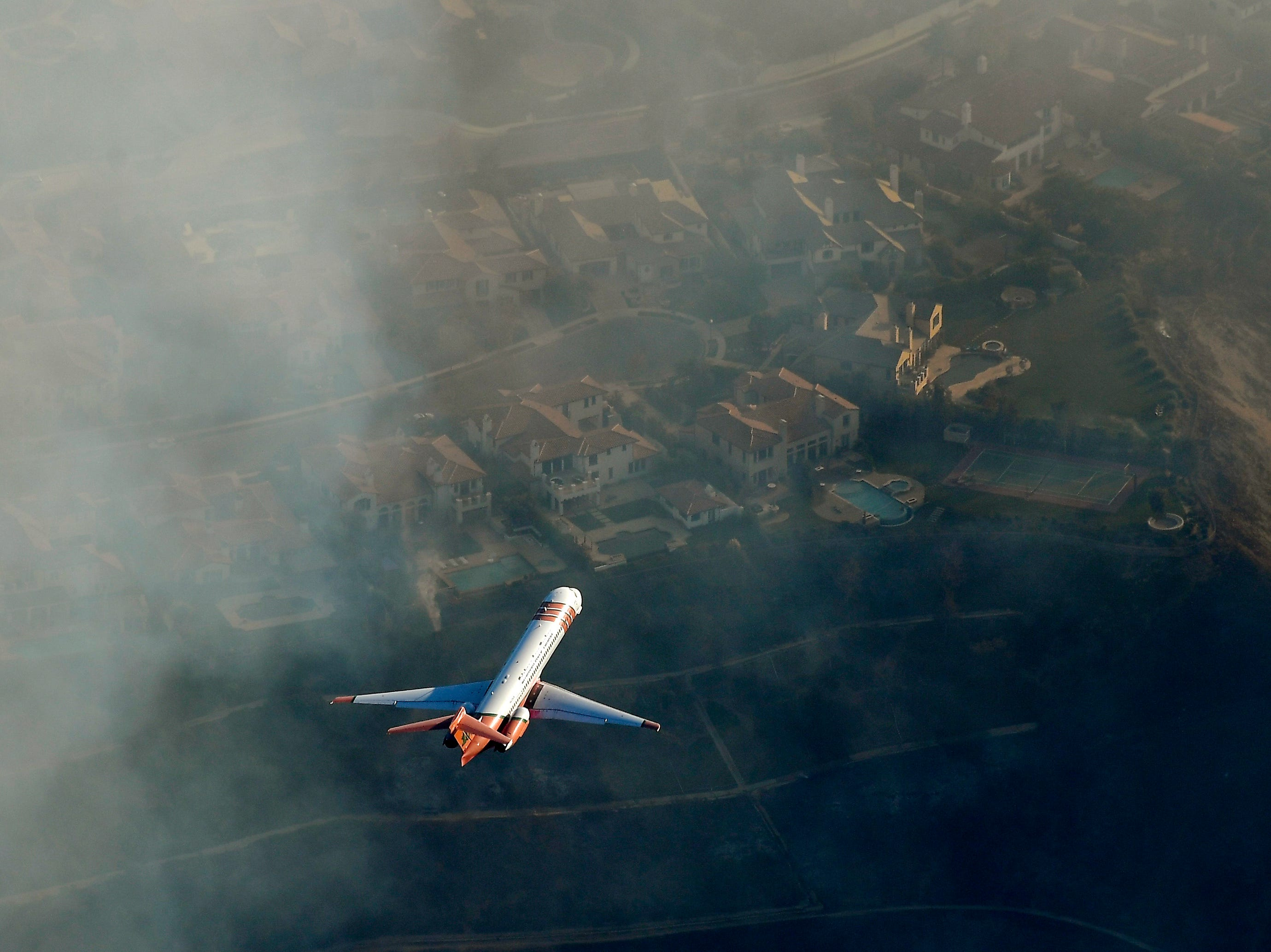 A DC-10 air tanker flies over homes as fires burn Friday as seen from a helicopter over Calabasas.
