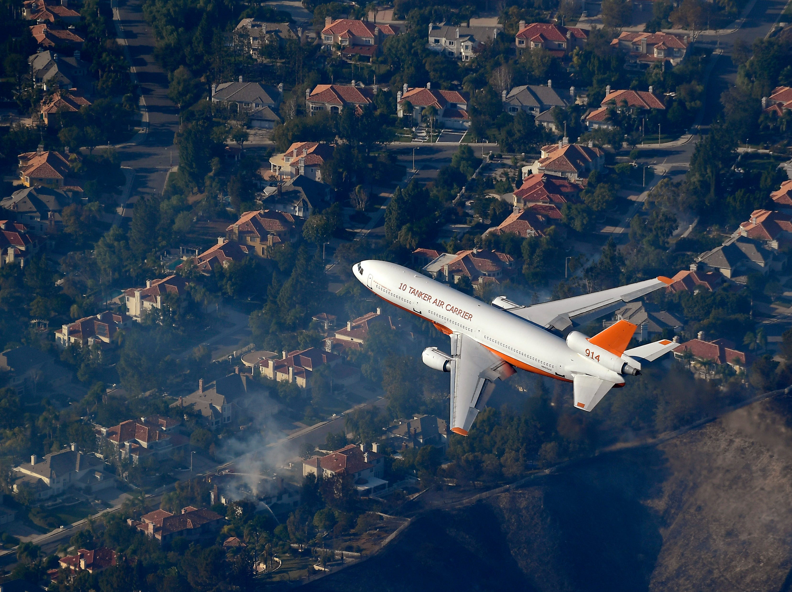 A DC-10 tanker flies over homes in Calabasas on Friday in efforts to fight the Woolsey Fire as it burned toward the ocean.