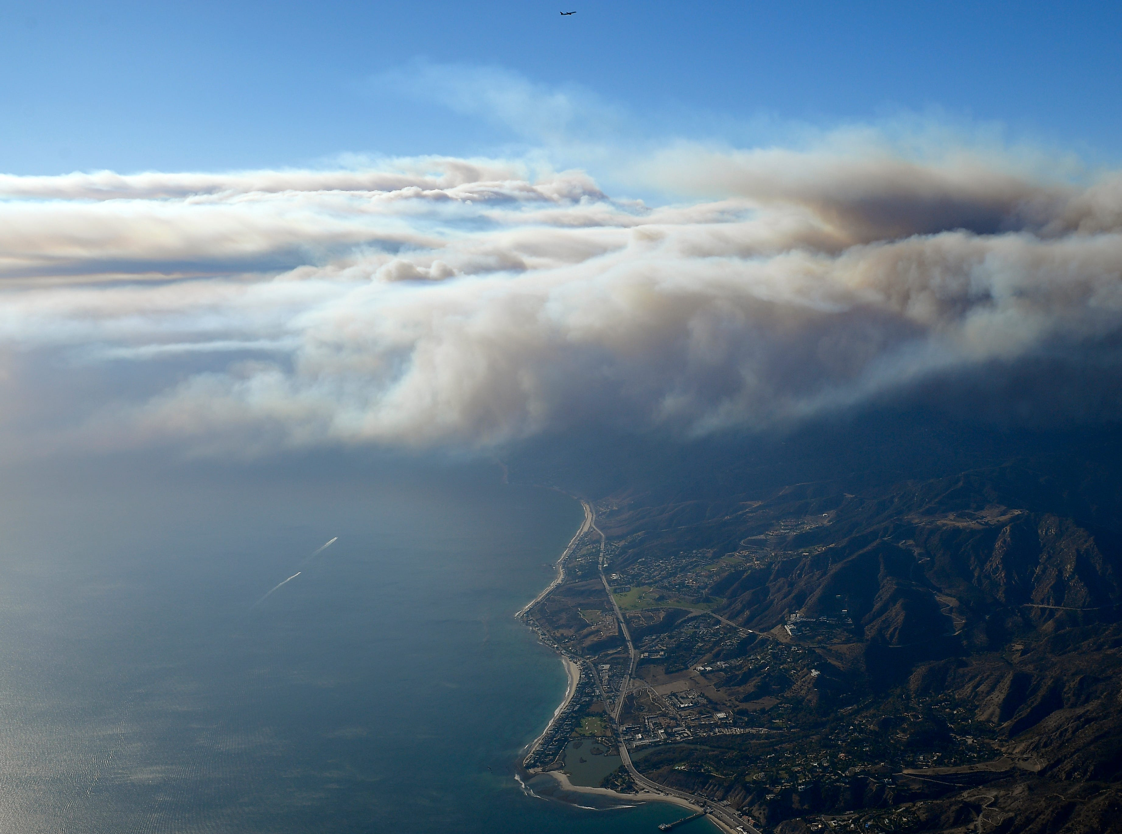 Smoke rises as the Woolsey and Hill fires burn toward the Pacific Ocean on Friday, as seen from a helicopter over Santa Monica.