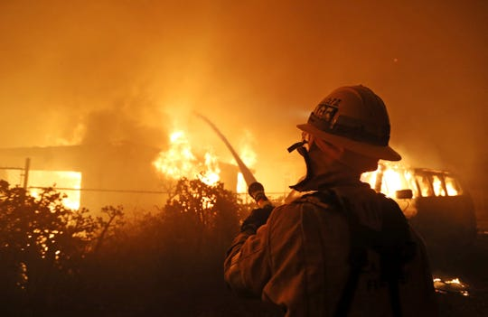 A firefighter does structure protection on a house behind him as flames from the Woolsey Fire consume a home on Dume Drive in the Point Dume area of Malibu on Friday.