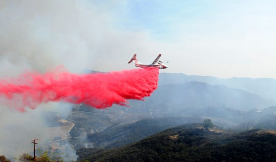 An airplane drops fire retardant on  houses near Mipolomol and Cotharin roads Saturday in the mountains of Ventura County. The Woolsey Fire continues to burn in the county.