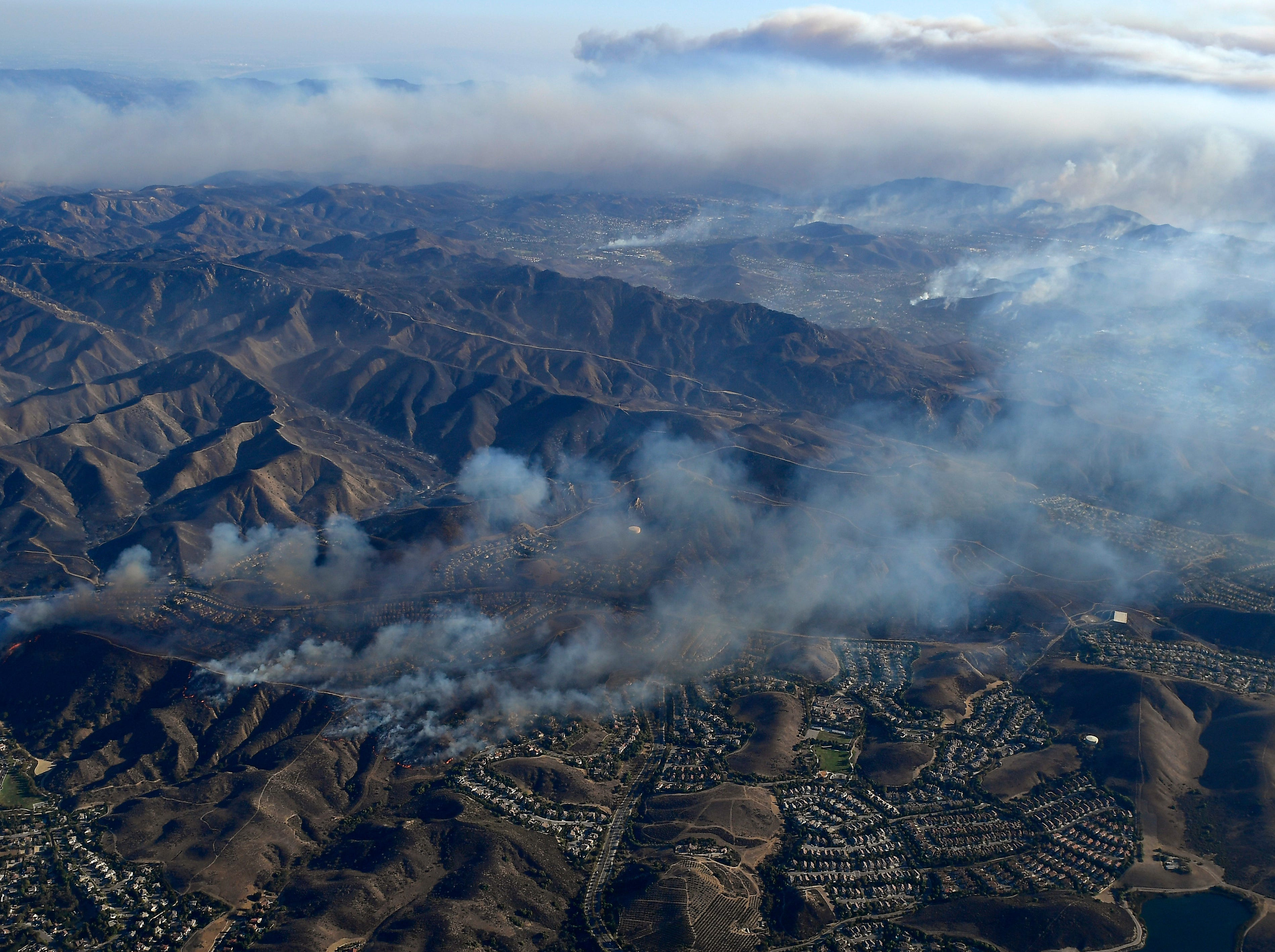 Smoke rises as the Woolsey and Hill fires burn toward the Pacific Ocean on Friday, as seen from a helicopter over Simi Valley.